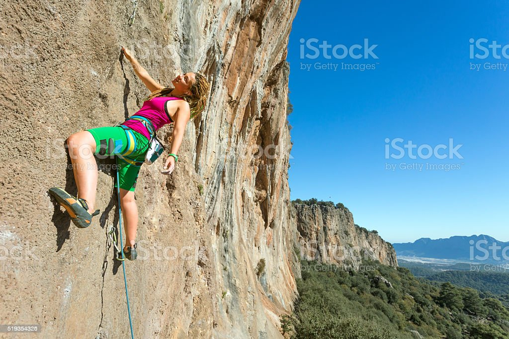 Youth female Rock Climber hanging on vertical Wall stock photo