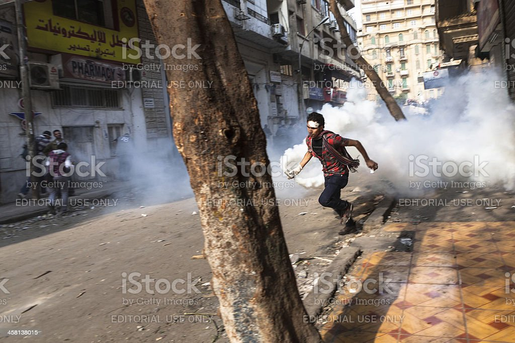 Youth fight back by stealing tear gas canisters in Tahrir stock photo