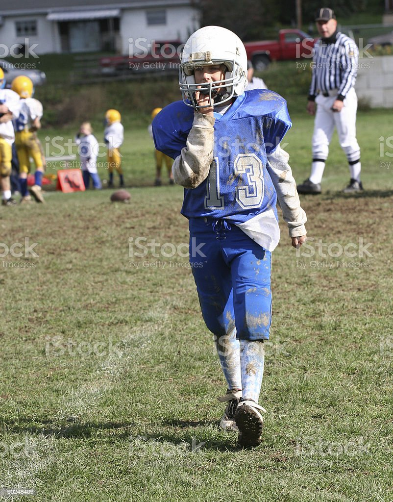 Youth Football Player Walking Off Field stock photo
