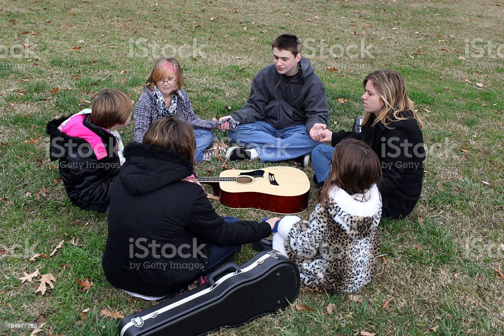 Youth group holding hands while sitting around a guitar stock photo