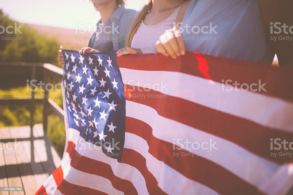 Youth holding an American flag outdoors stock photo