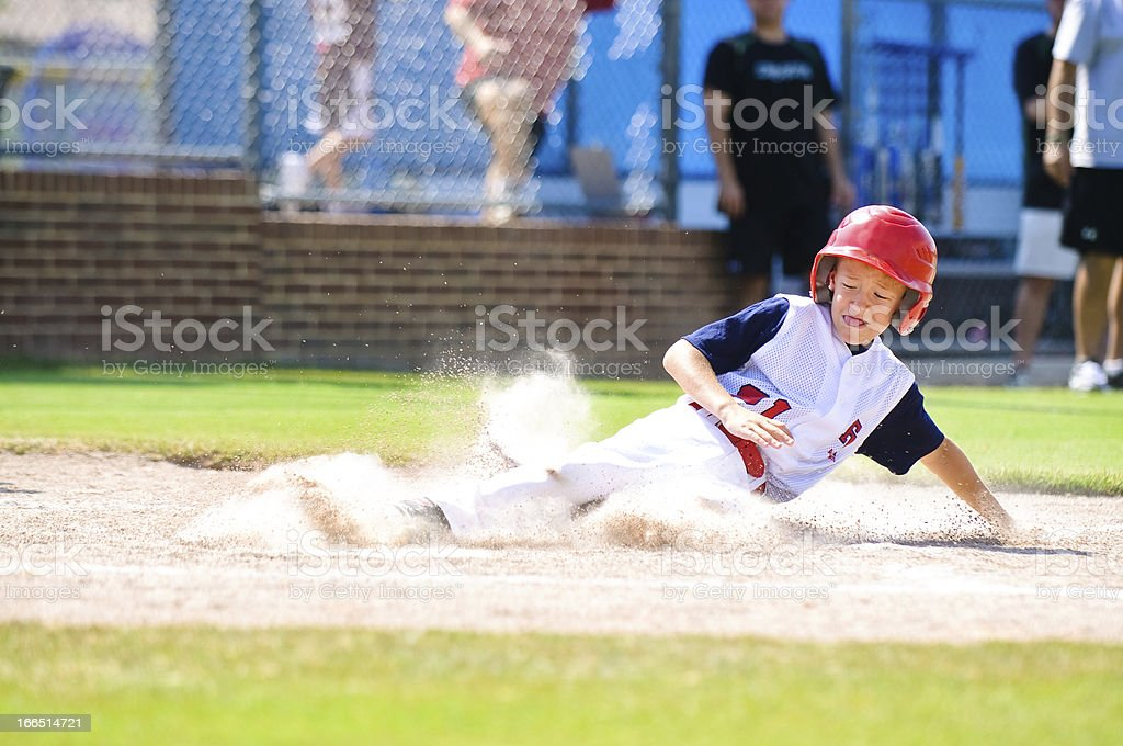 Youth league baseball player sliding home. stock photo