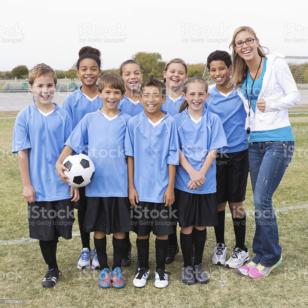 Youth league soccer team posing with coach after game royalty-free stock photo