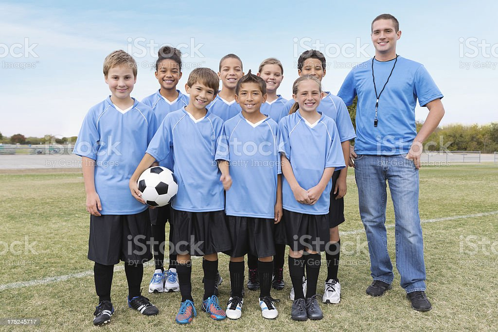Youth league soccer team posing with coach before game stock photo