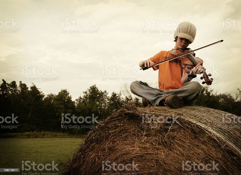 Youth playing a fiddle on top of a giant hay bale royalty-free stock photo