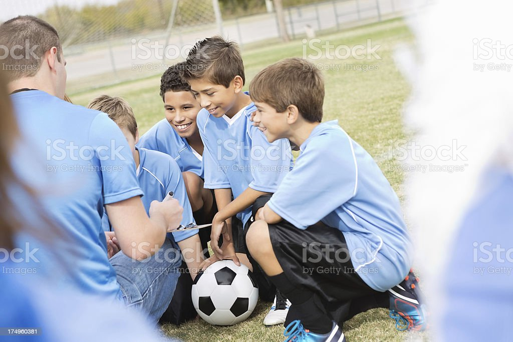 Youth soccer team huddled with coach during game royalty-free stock photo
