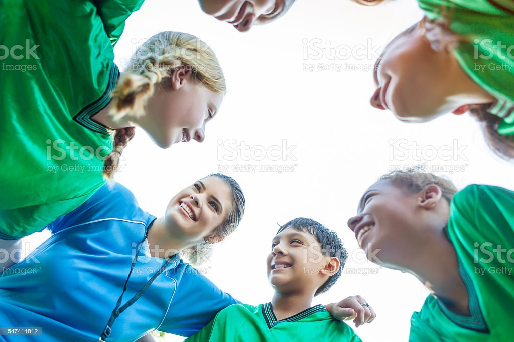 Youth soccer team huddles up during time out stock photo