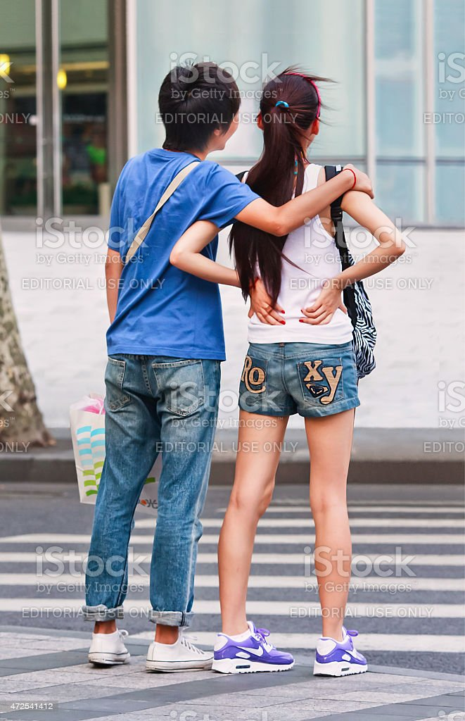 Youthful couple waiting to cross a zebra path, Shanghai, China stock photo