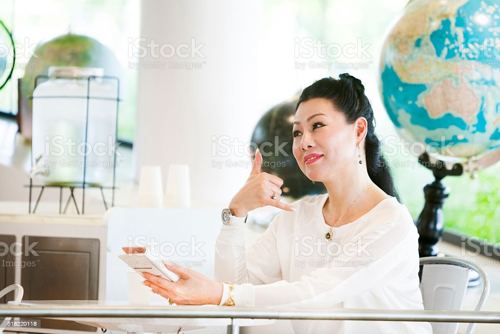 Youthful Senior Asian Woman Friendly Gesturing To Her Colleagues stock photo