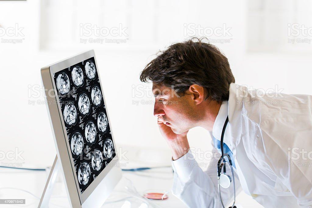 Yung male doctor  watching CAT scan image of human abdomen stock photo