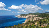 Zakynthos cliff panorama with clear water, blue sky and white