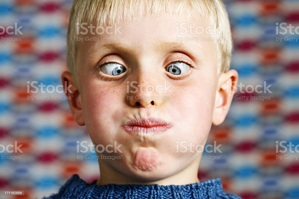 Zany 7 year old boy, cross-eyed and grimacing stock photo