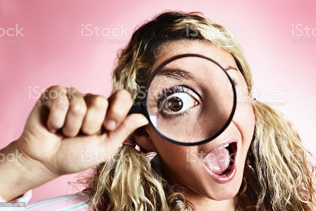 Zany blonde looks through magnifying glass with hugely enlarged eye royalty-free stock photo