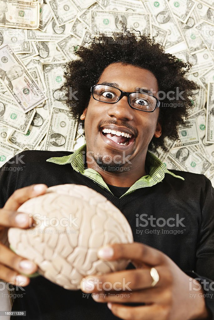 Zany geek holding model brain and lying on dollars royalty-free stock photo