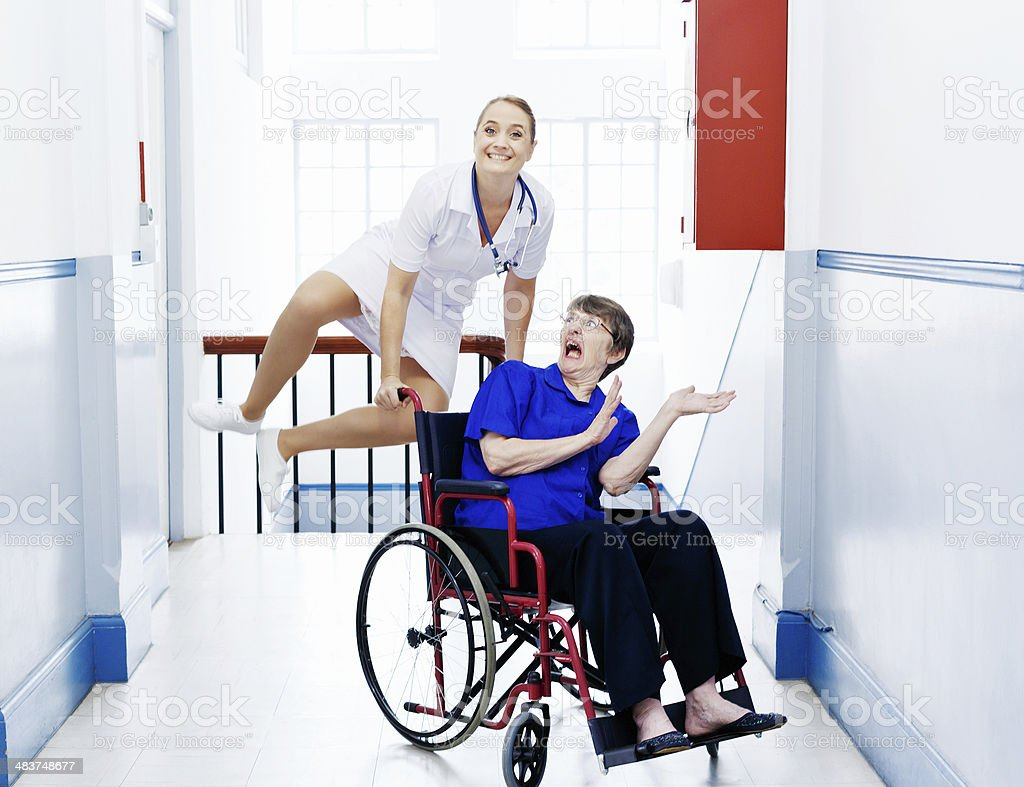 Zany image: nurse leaps over terrified old woman in wheelchair stock photo