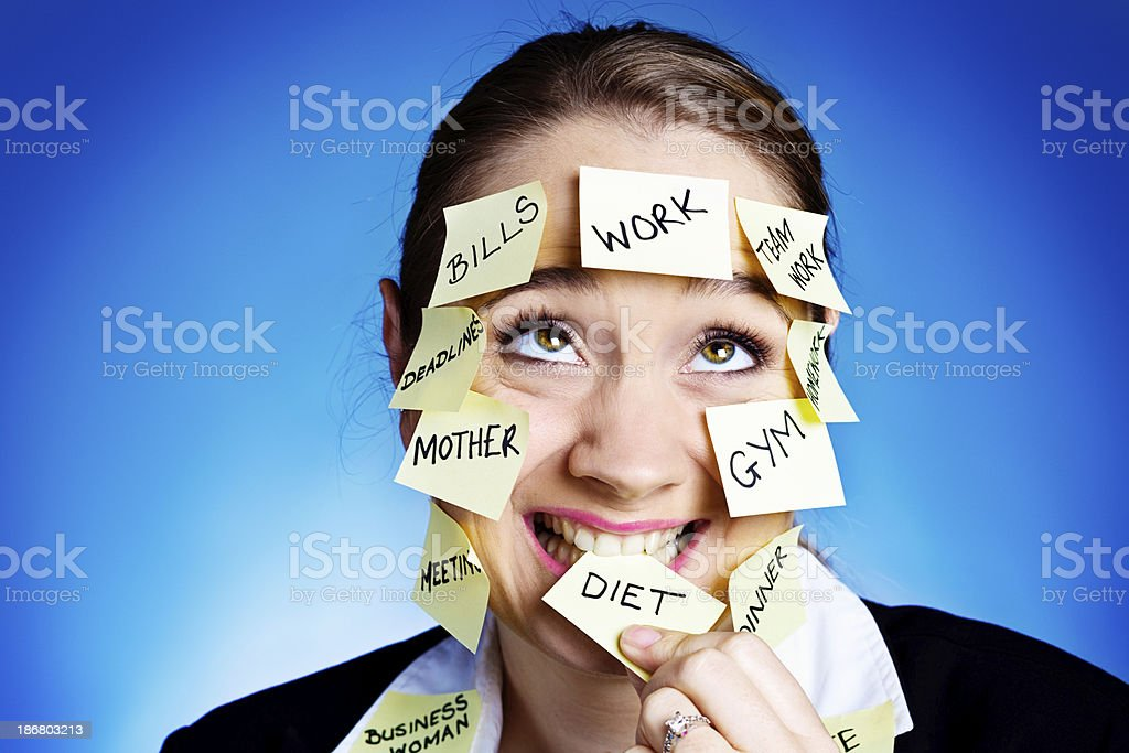 Zany woman covered in  task reminders nibbles Diet reminder stock photo