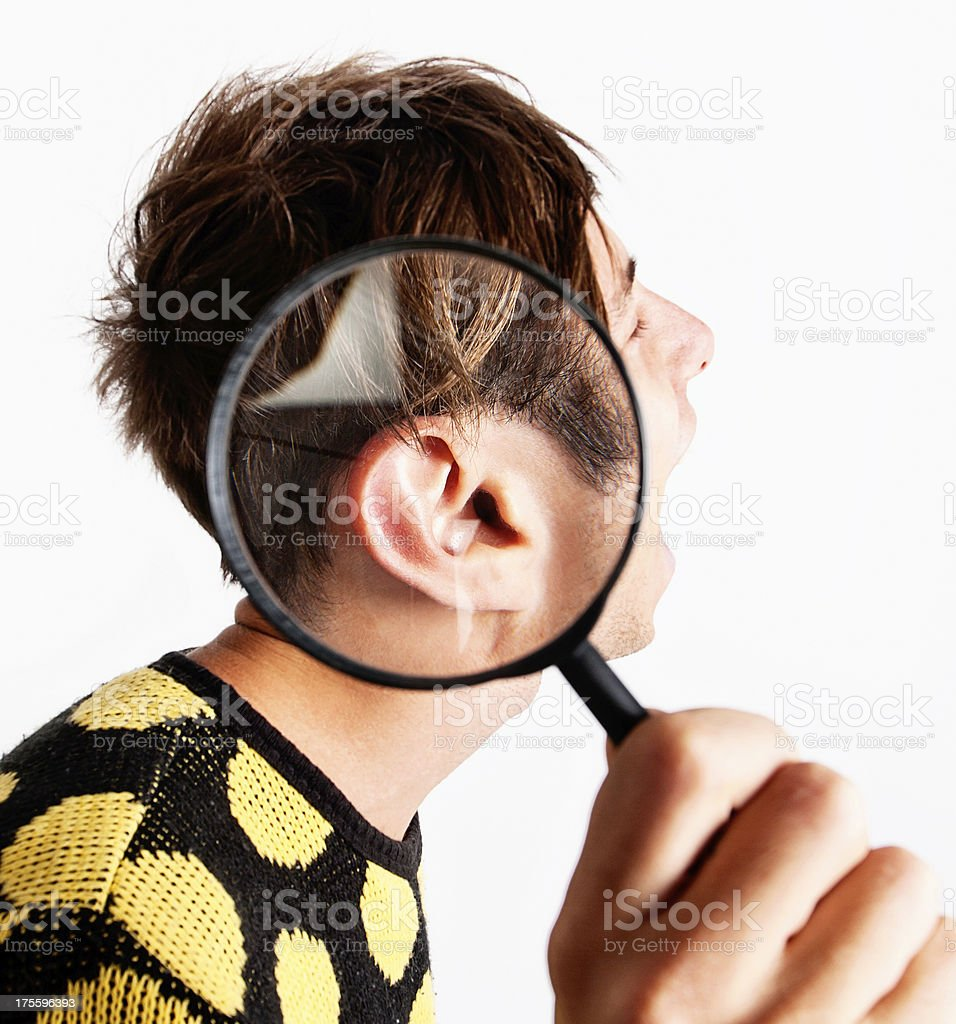 Zany young man with magnifying glass over ear stock photo