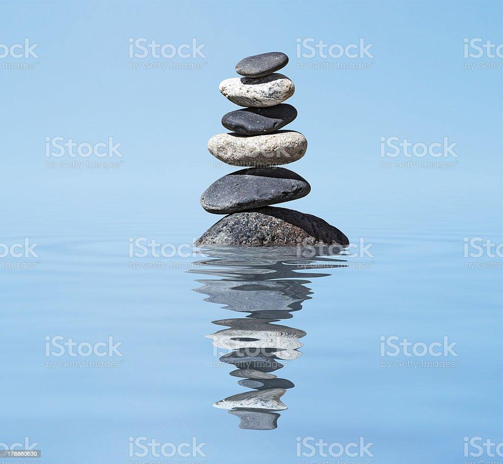 Zen balanced stones stack in lake  balance peace silence concept stock photo