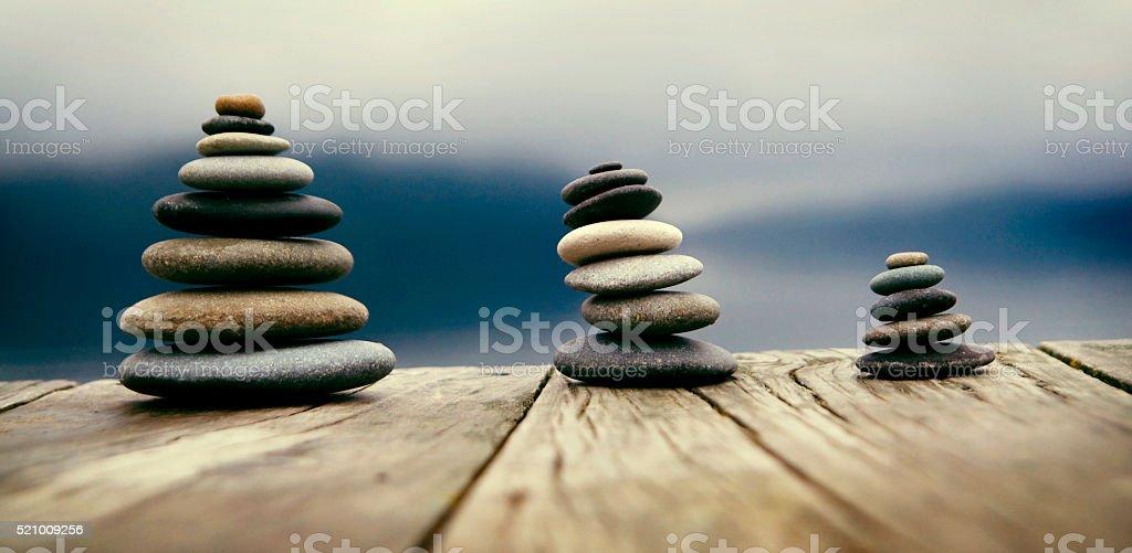 Zen Balancing Pebbles Next to a Misty Lake Concept stock photo