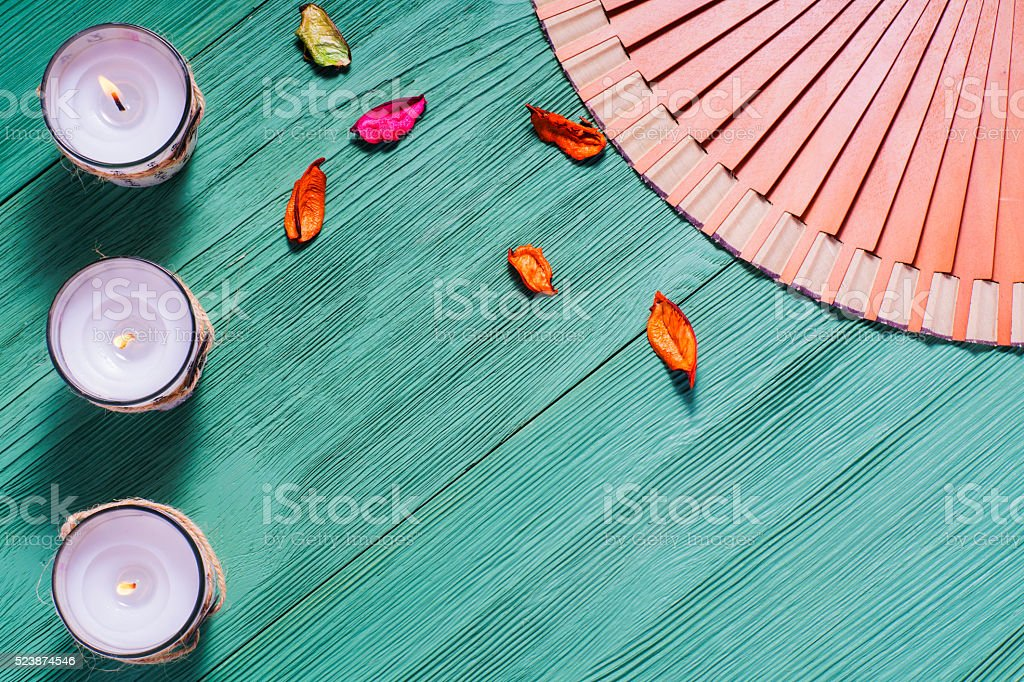 Zen candle and fan with hieroglyphs on a  wooden background stock photo