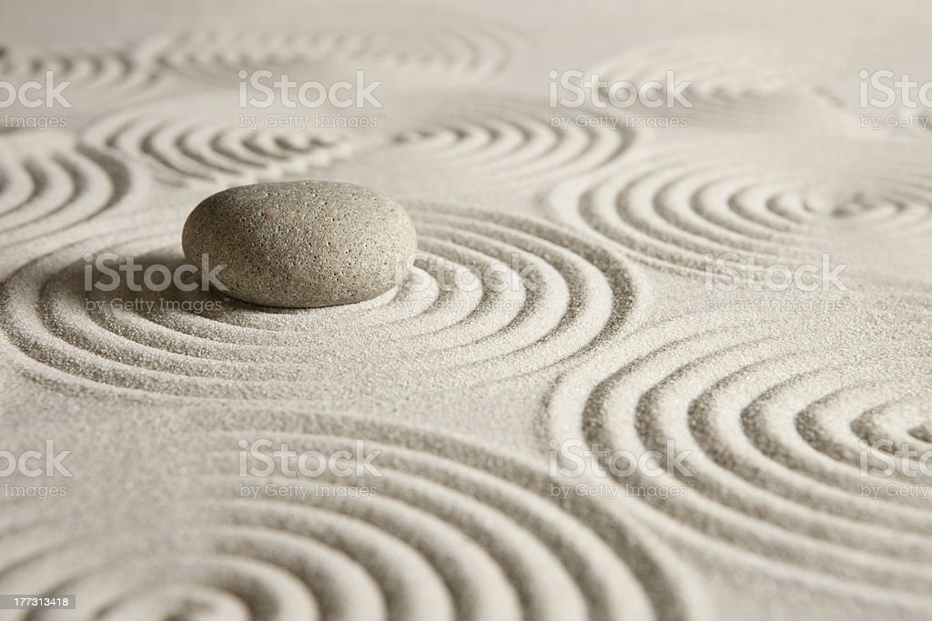 Zen garden Beige round stone on carefully arranged sand stock photo