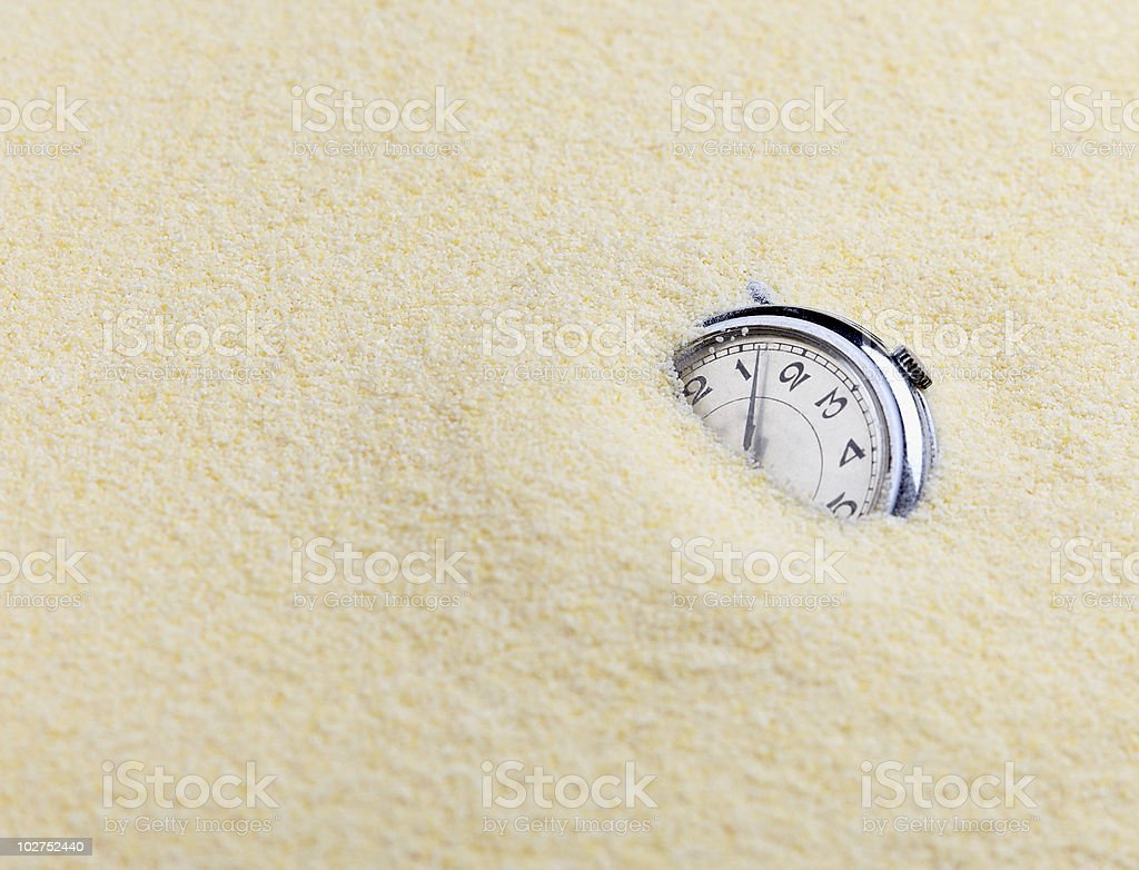 Zen garden composition with white sand engulfing a timepiece royalty-free stock photo