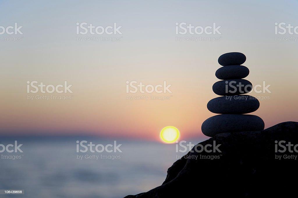 Zen pebble stack at sunset stock photo
