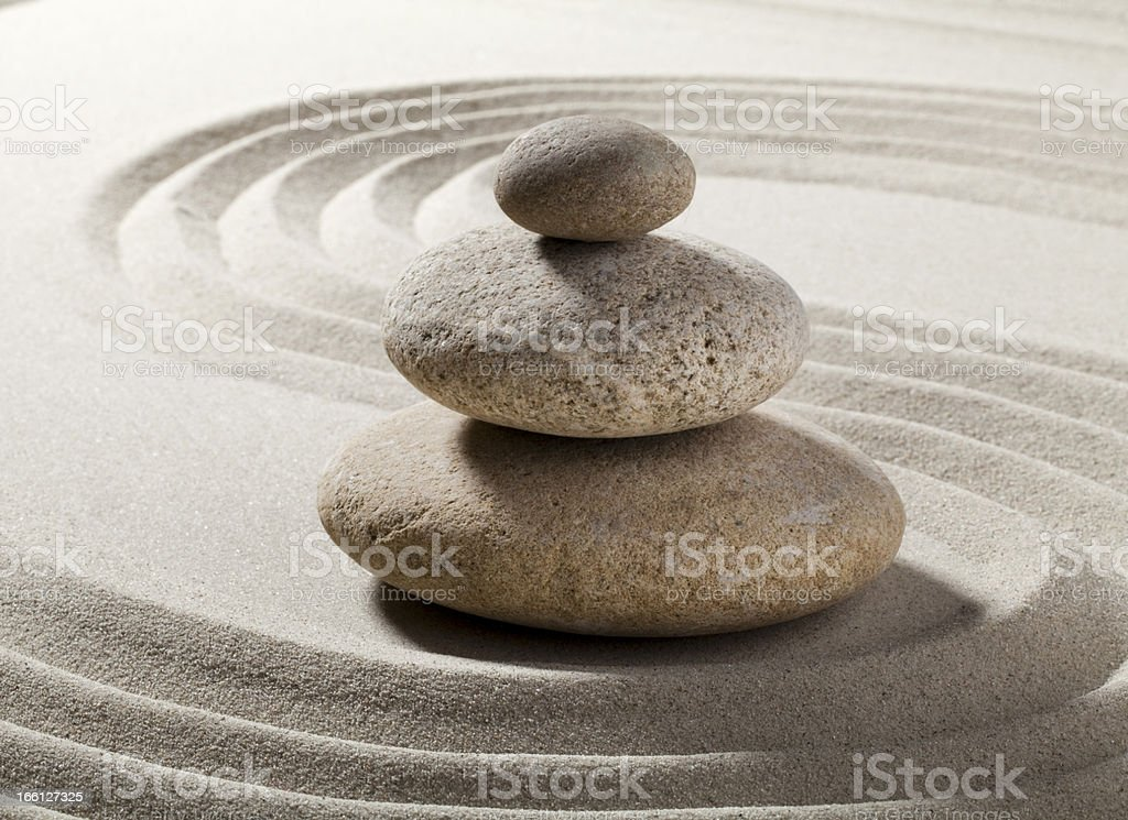 Zen relaxation pebbles in swirled sand. royalty-free stock photo