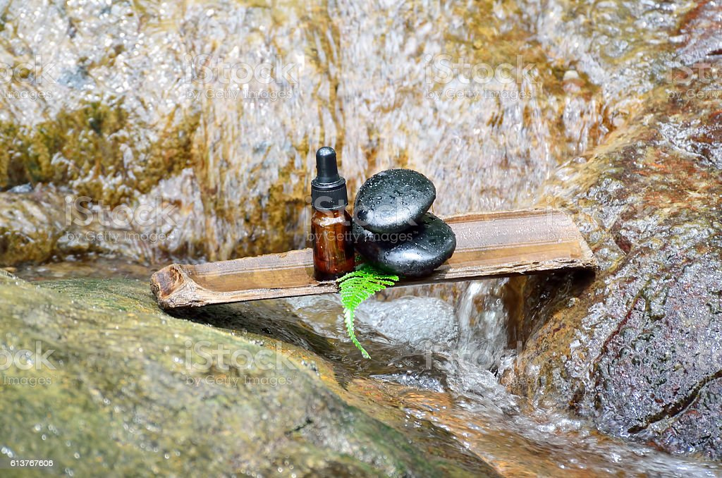 Zen stone with spa oil in SPA concept at waterfall stock photo