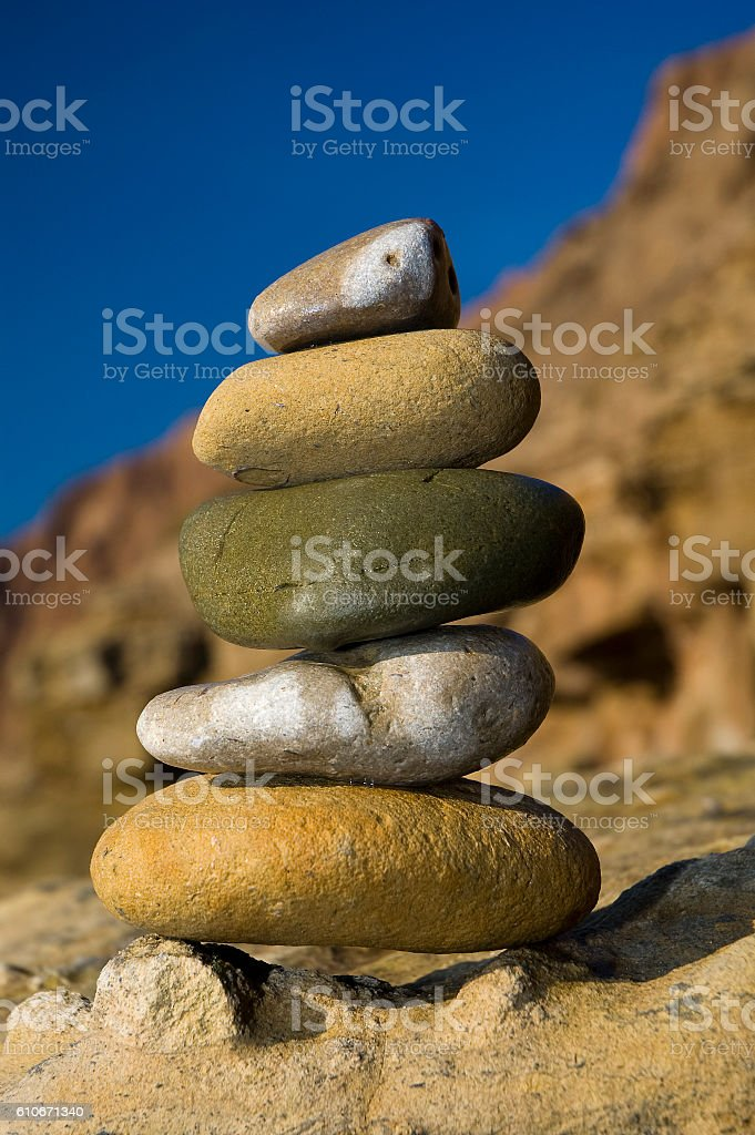 Zen style stack of rocks against a vivid blue sky stock photo