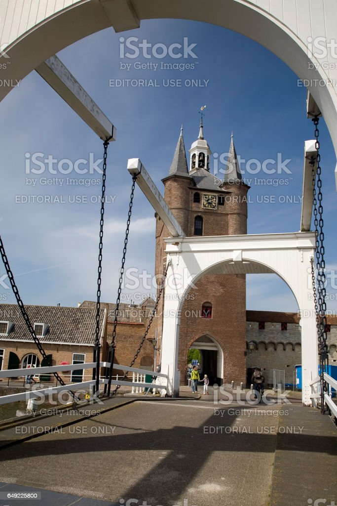 Zierikzee, Netherlands - May 6th, 2009: Mature woman with child walking and mature man cycling near North- and Southharbourgate stock photo