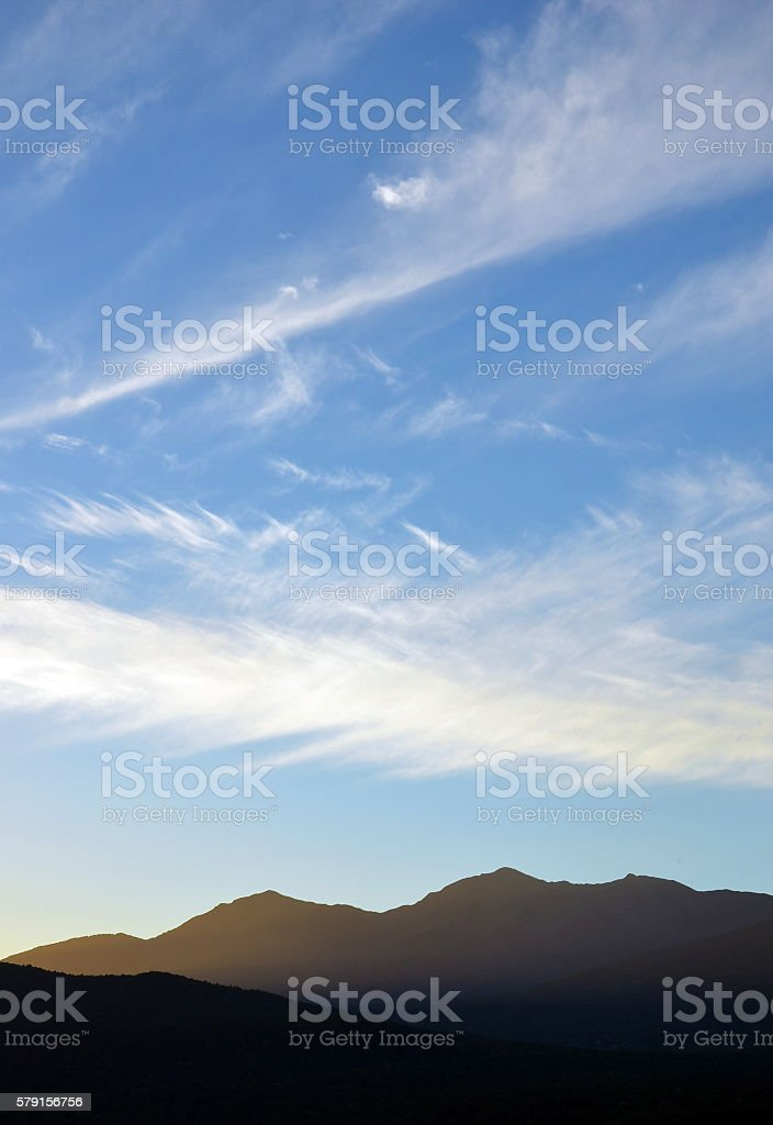 Zigzag cloud patterns in the sky above mountains at dusk stock photo