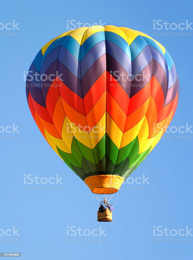 A zigzag colorful hot air balloon isolated on a blue sky stock photo