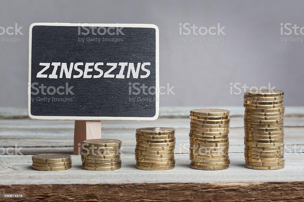 Zinseszins (compound interests) in German, chalk blackboard and money stacks stock photo