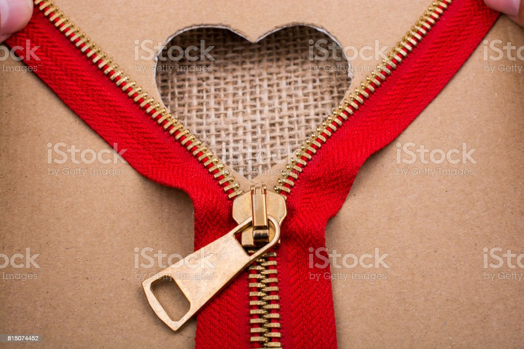 Zipper and heart shape hole on paper stock photo