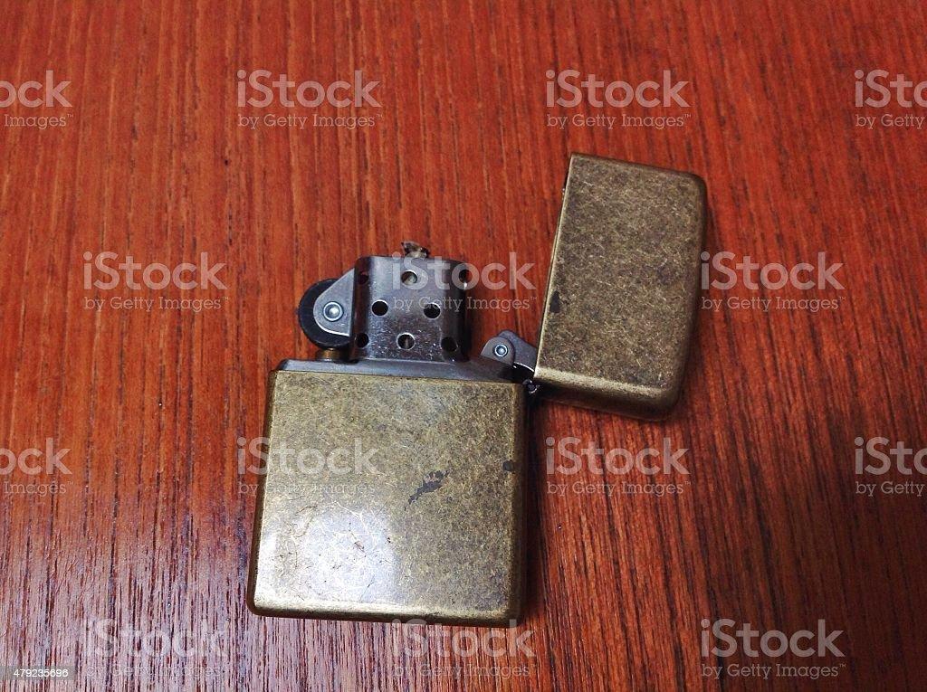 Zippo wind proof lighter aged brass on teak wood surface stock photo