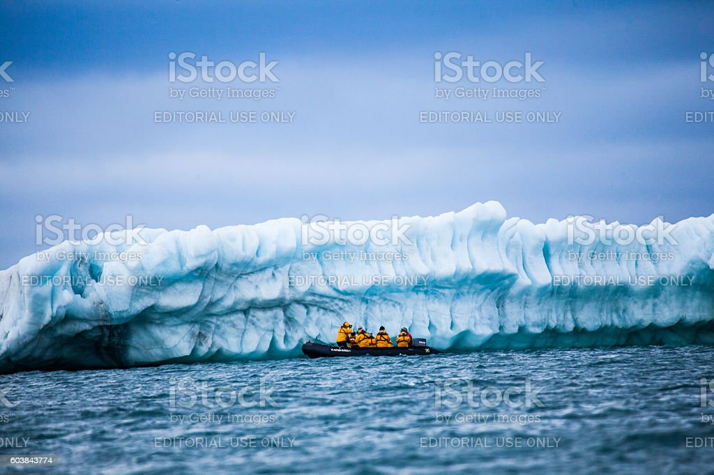 Zodiak with tourists in front of Iceberg arctic ocean stock photo