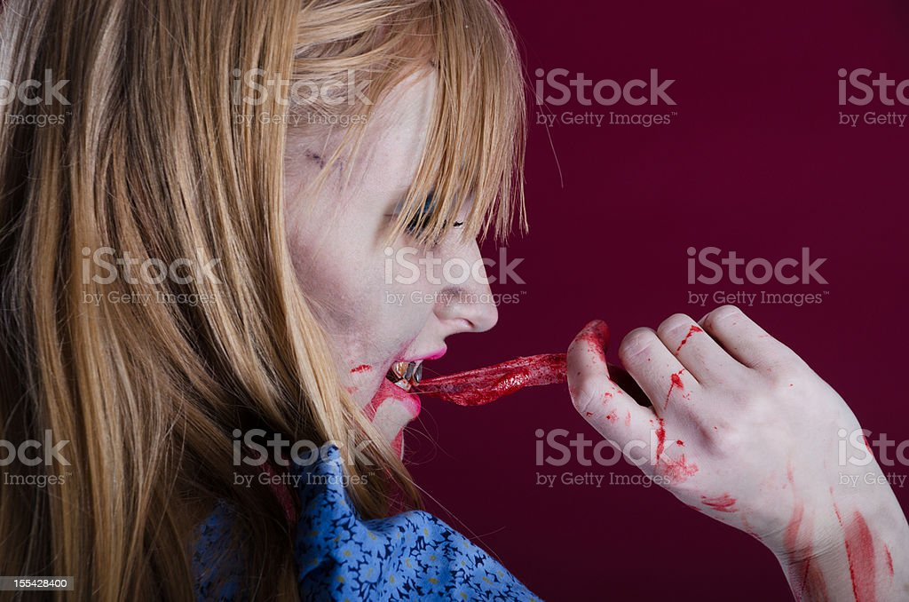 Zombie Alice biting strip of flesh, side view. stock photo