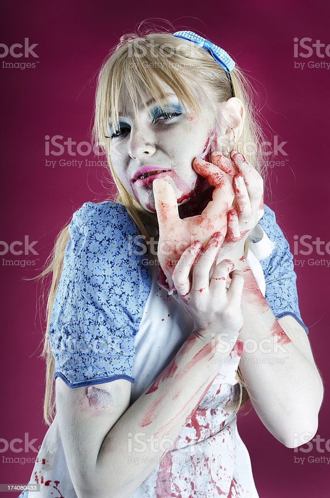 Zombie Alice caressing face with detached hand. royalty-free stock photo