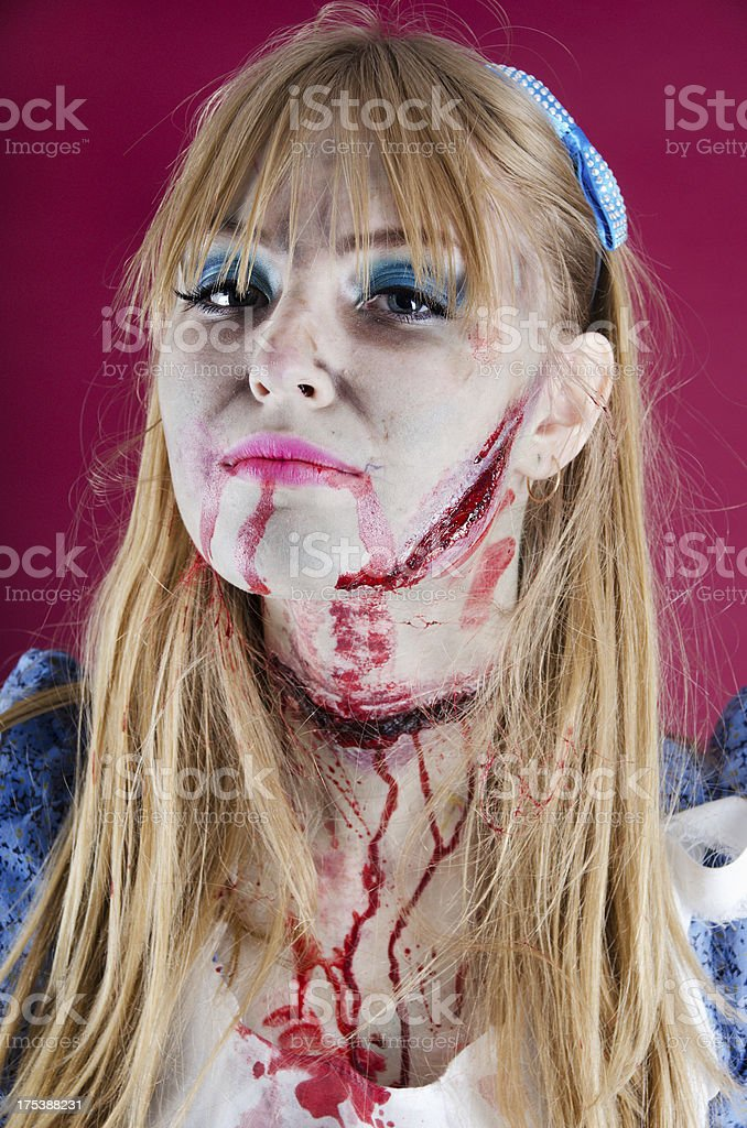 Zombie Alice, head tilted to show wounds. stock photo