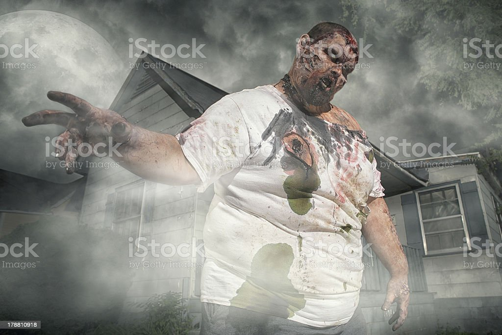 Zombie coming out of an old abandoned house royalty-free stock photo