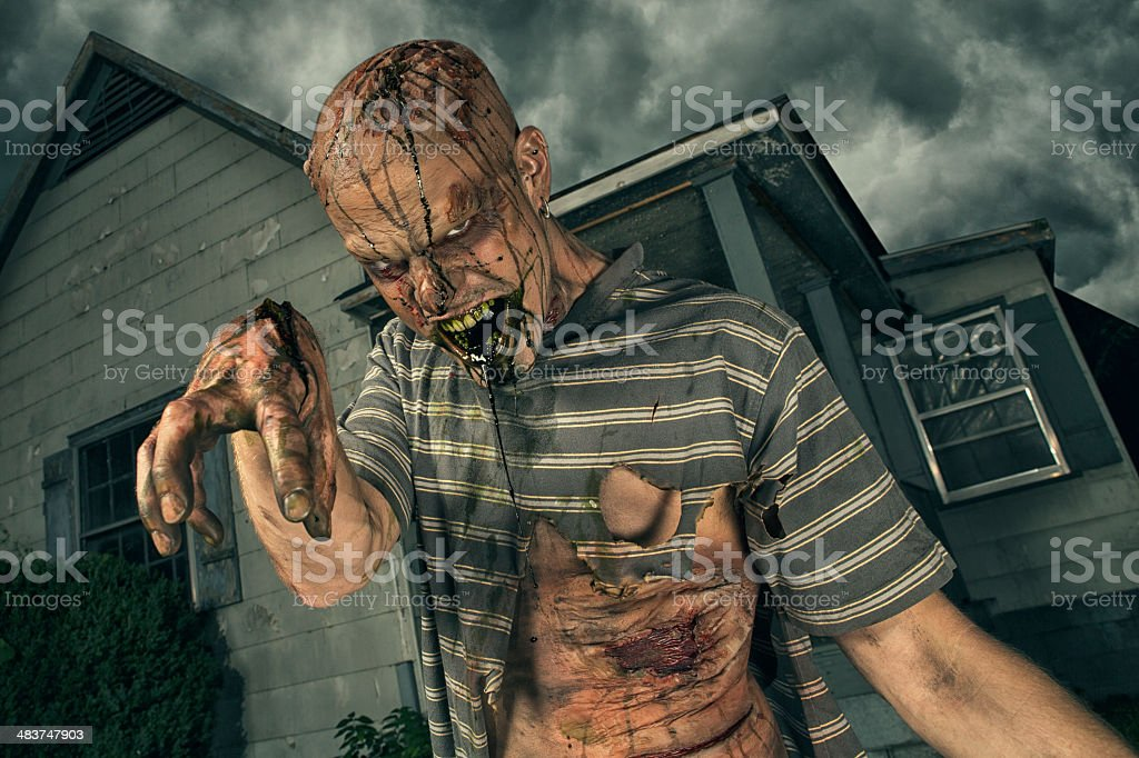 Zombie coming out of an old abandoned house stock photo
