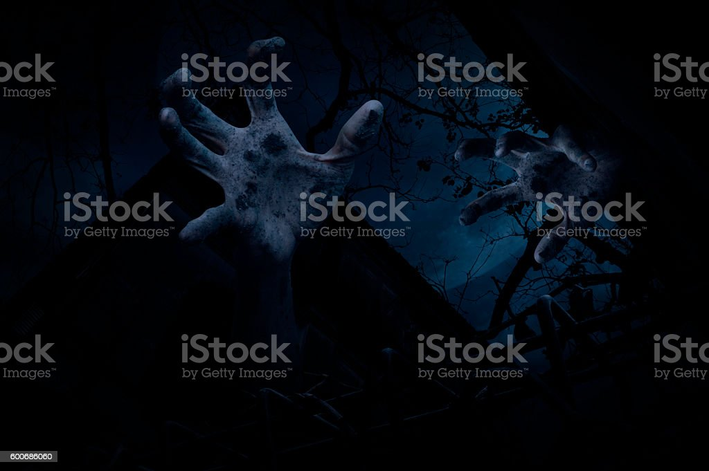 Zombie hand rising out from old castle over cloudy sky stock photo