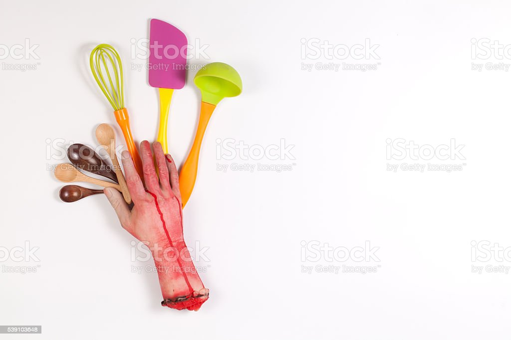 Zombie Hand with kitchen utensils on white background stock photo