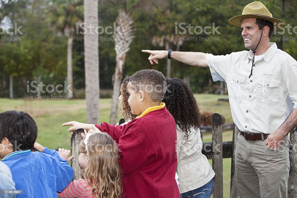 Zoo keeper with group of children at animal exhibit stock photo