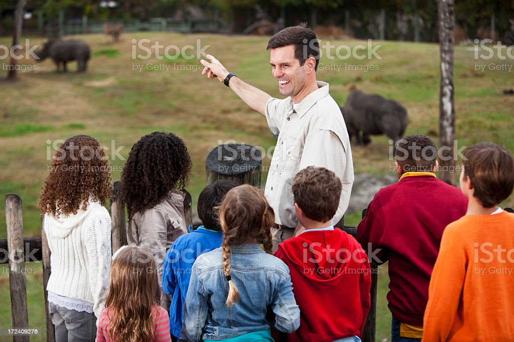 Zoo keeper with group of children at rhino exhibit stock photo