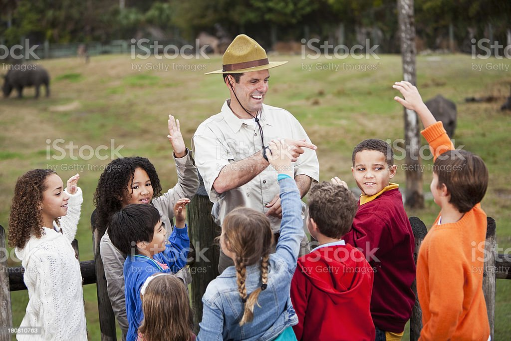 Zoo keeper with group of children at rhino exhibit royalty-free stock photo