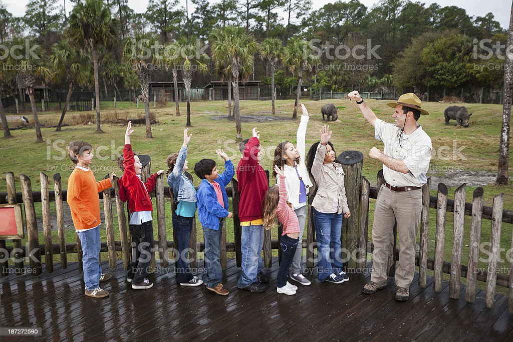 Zoo keeper with group of children on field trip stock photo