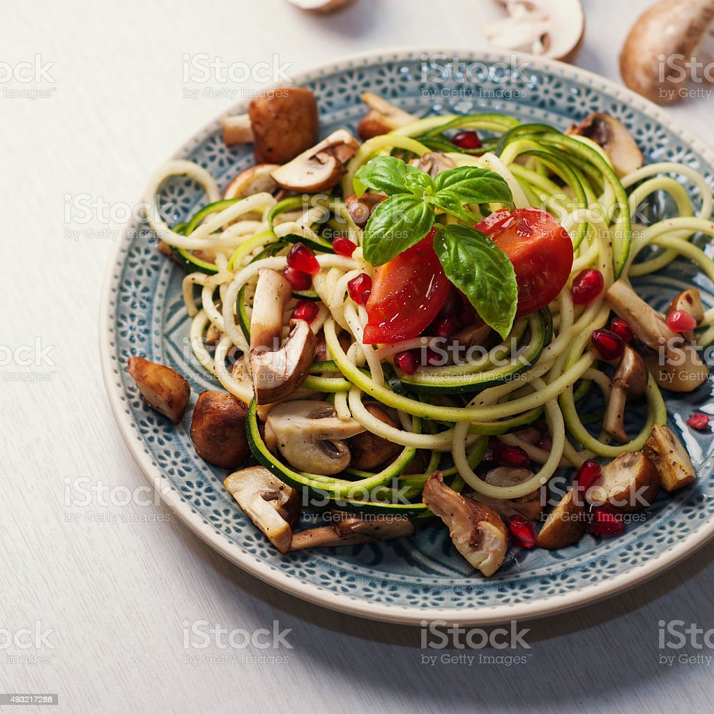 Zoodles with mushrooms and pomegranate seeds stock photo