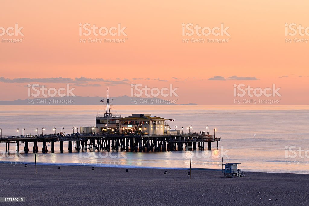 Zoomed out view of lit up Santa Monica Pier in evening stock photo
